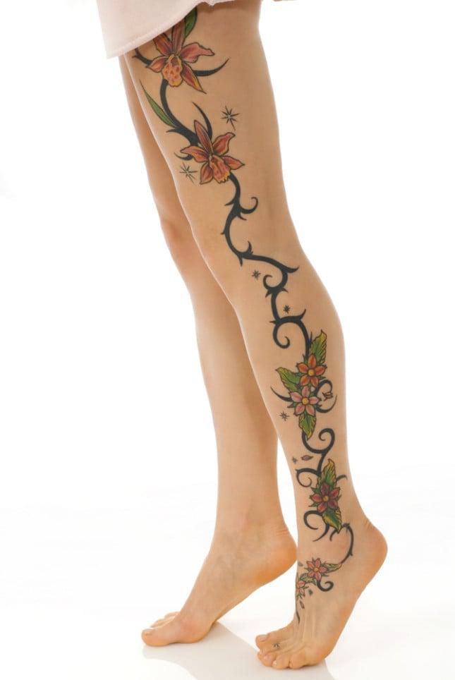 Tatuaggio su tutta la gamba con fiori e rami