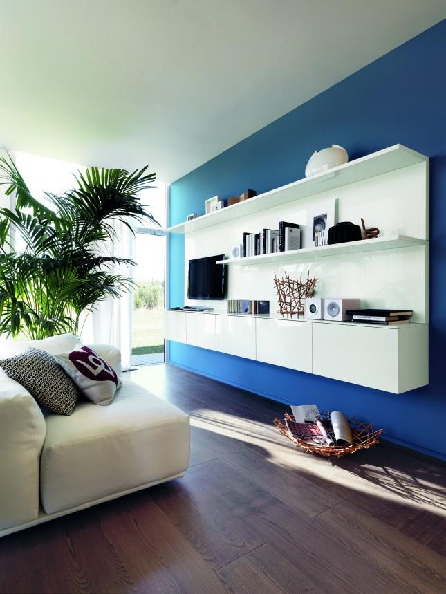 Soluzione sospesa per questa ambientazione living di LiberaMente, con ripiani, mensole e pensili con anta laccata lucida color Bianco Prestige