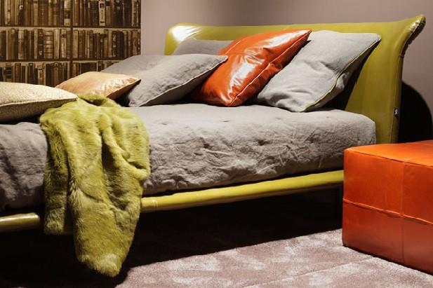Verde oliva il letto matrimoniale modello Calvin di Twils e arancio per il cuscino in pelle e puff-comodino: un accostamento di carattere e di gran moda