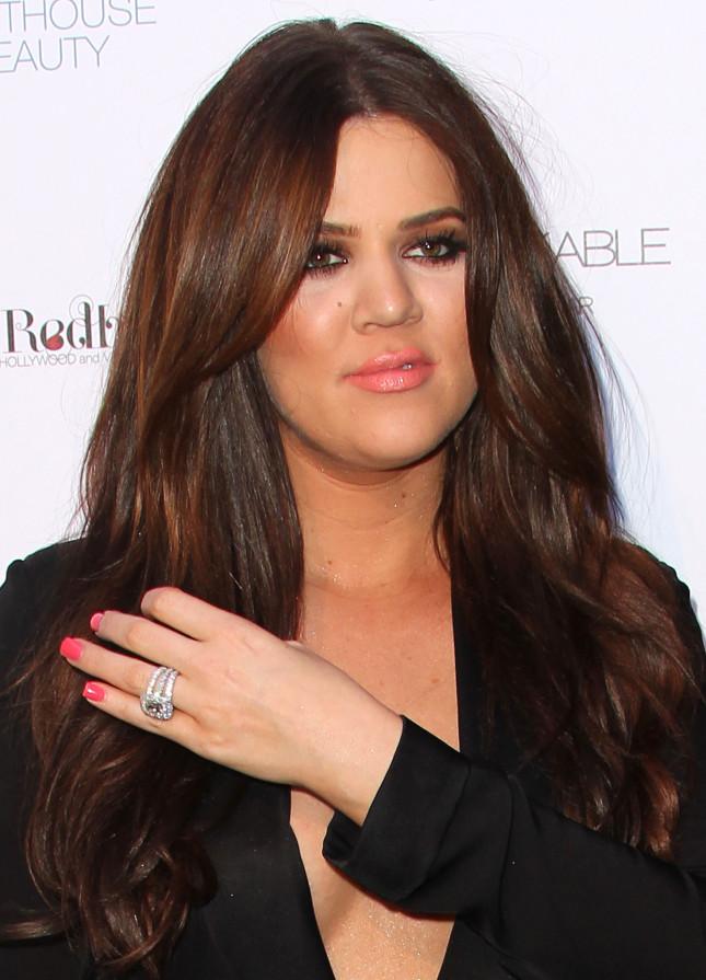 Kloe Kardashian sfoggia sorridente il suo anello di fidanzamento in occasione del lancio del suo profumo