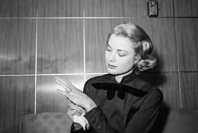 Grace Kelly posa in una foto in bianco e nero e sembra in contemplazione del suo bellissimo anello di fidanzamento