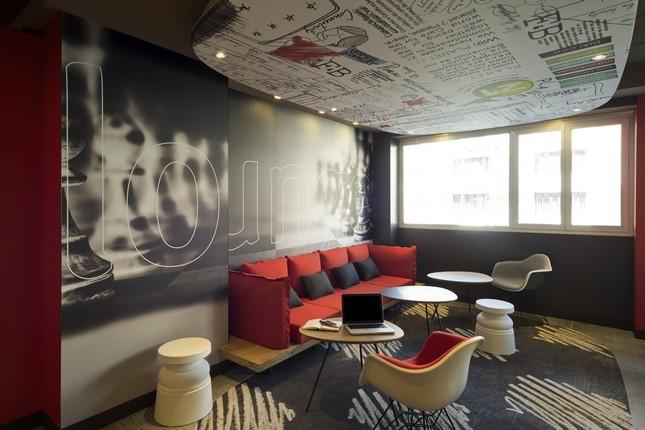 Rosso, nero e grigio con qualche tocco di bianco: la lounge dell'ibis Milano Centro