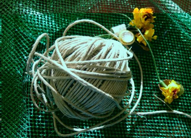 Ecco i materiali per abbellire la tua palla di neve: una retina verde glitterata, fiorellini gialli, un bottone-gioiello e, perché no, dello spago al posto del tradizionale nastro, per creare un effetto ancora più shabby-chic