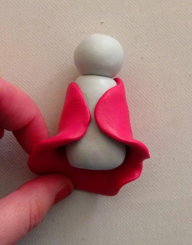 Avvolgi un pezzo di fimo rosso cherry appiattito attorno al busto del pupazzo di neve per creare una mantellina
