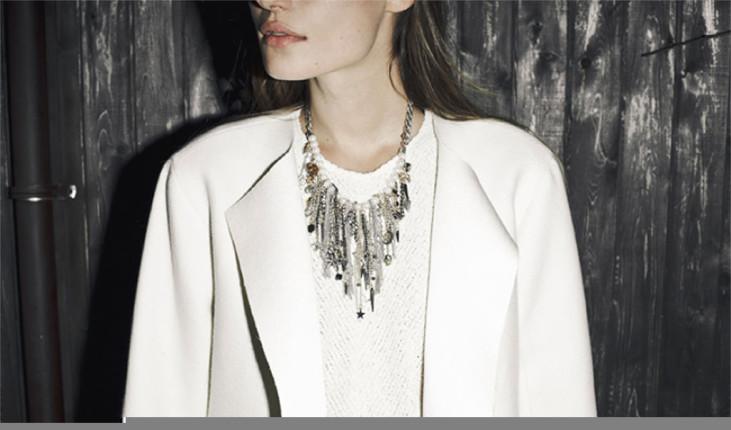 Blazer bianco indossato con maglia tono su tono e impreziosito con una collana di ciondoli. Zara.