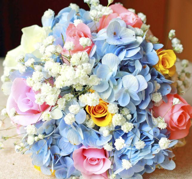 Bouquet dai colori pastello: velo da sposa, ortensia azzurra e roselline multicolor