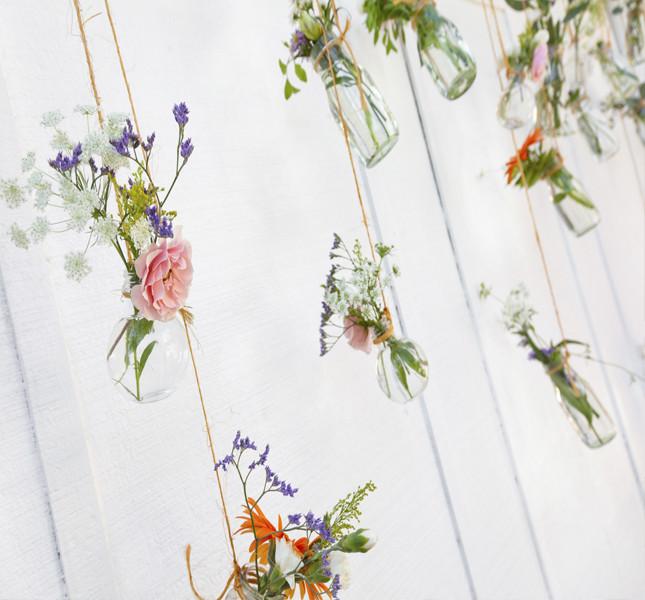 Vasetti e fiori appesi a un albero: un tableau originale da proporre all'aperto!
