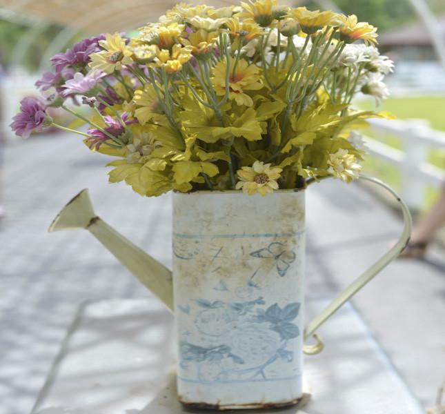 Un innaffiatoio usato come vaso per i decorazioni country