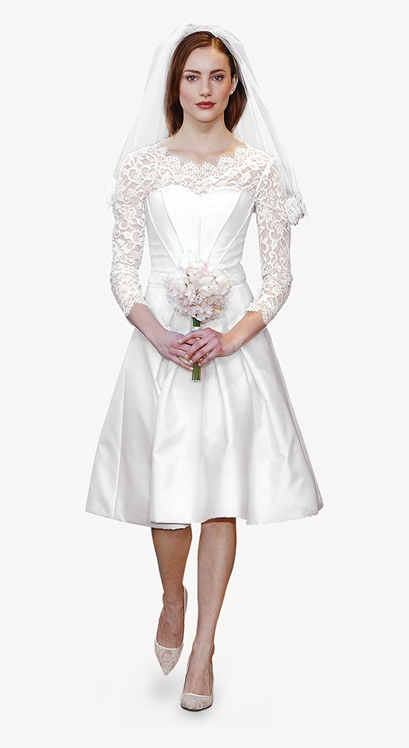 La stilista Carolina Herrera propone un vestito con gonna a ruota in tessuto mikado e in pizzo nella parte superiore, con velo corto di tulle e bordo in pizzo. Un abito che ci porta ad assaporare un'atmosfera d'altri tempi