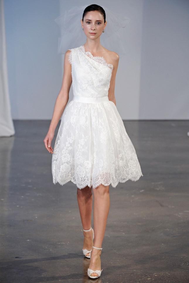 Marchesa propone questo delicato abito con gonna a ruota e lunghezza sopra il ginocchio, monospalla rifinito con pizzo smerlato bianco candido