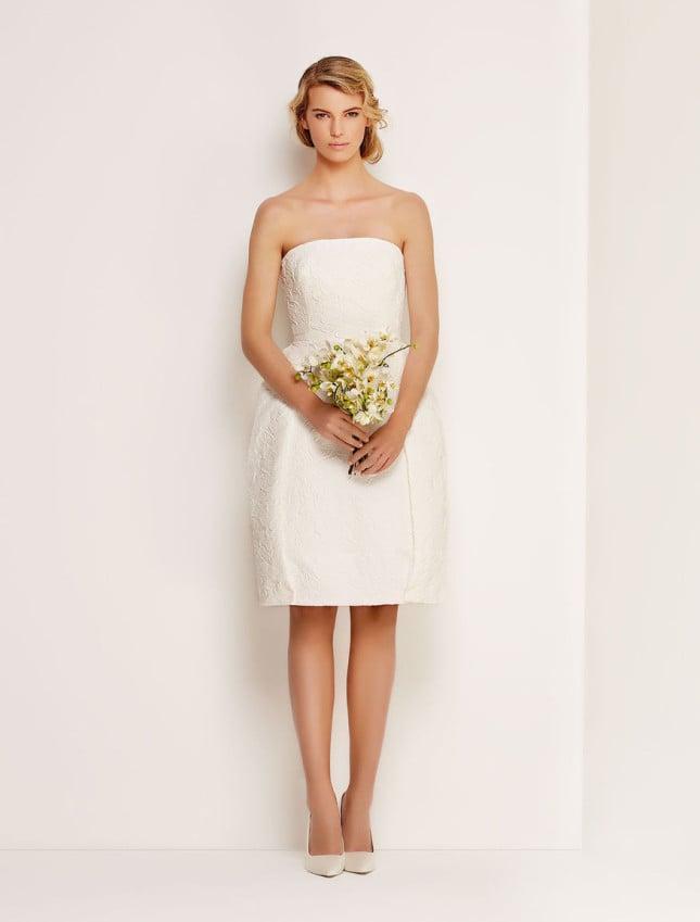 Il modello Peonia della collezione Bridal di Max Mara è un tubino semplice, senza spalline ma con silhouette a clessidra, il tessuto è avvolto da ricco pizzo adornato