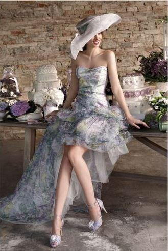 Vestito di Emé, con fantasia floreale su gonna a strati più corta davanti e con strascico dietro
