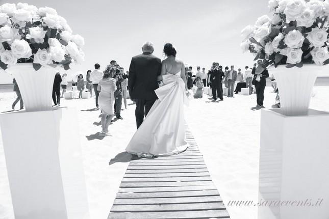 Una sposa cammina sulla spiaggia per incontrare il suo sposo - Sara Events