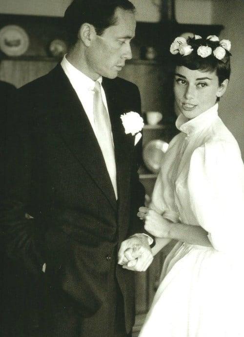 Audrey Hepburn sorride assieme al neo sposo Mel Ferrer in occasione del suo primo matrimonio, nel 1954. Indossa un abito di Givenchy con vita strettissima e gonna ampia a ruota sotto il ginocchio
