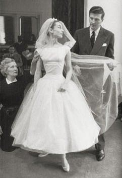 Audrey Hepburn sorride assieme al co-protagonista Fred Astaire nel 1957 sul set cinematografico del film Funny Face. Indossa un abito di Givenchy con raffinata gonna ampia in tulle da ballerina e corpetto con scollo a barchetta, un abito che rispecchia appieno lo stile del tempo.