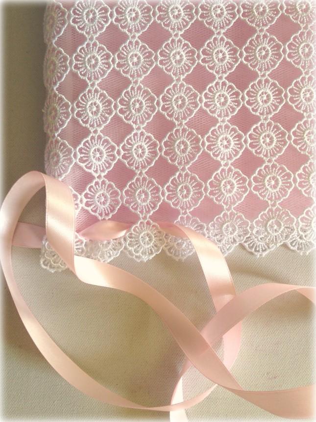 Passa il nastro rosa anche nei buchi del pizzo macramè dell'altra estremità