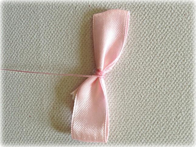 Infila l'ago in centro e crea un bel fiocco annodando bene il filo di cotone