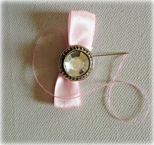 Sempre con ago e filo fissa il bottoncino gioiello al fiocco di raso rosa