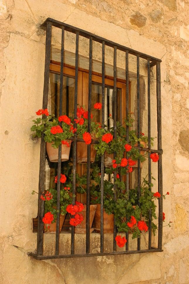 Balcone fiorito con gerani di color arancio acceso in piccoli vasi: siamo a Pedraza, Segovia.