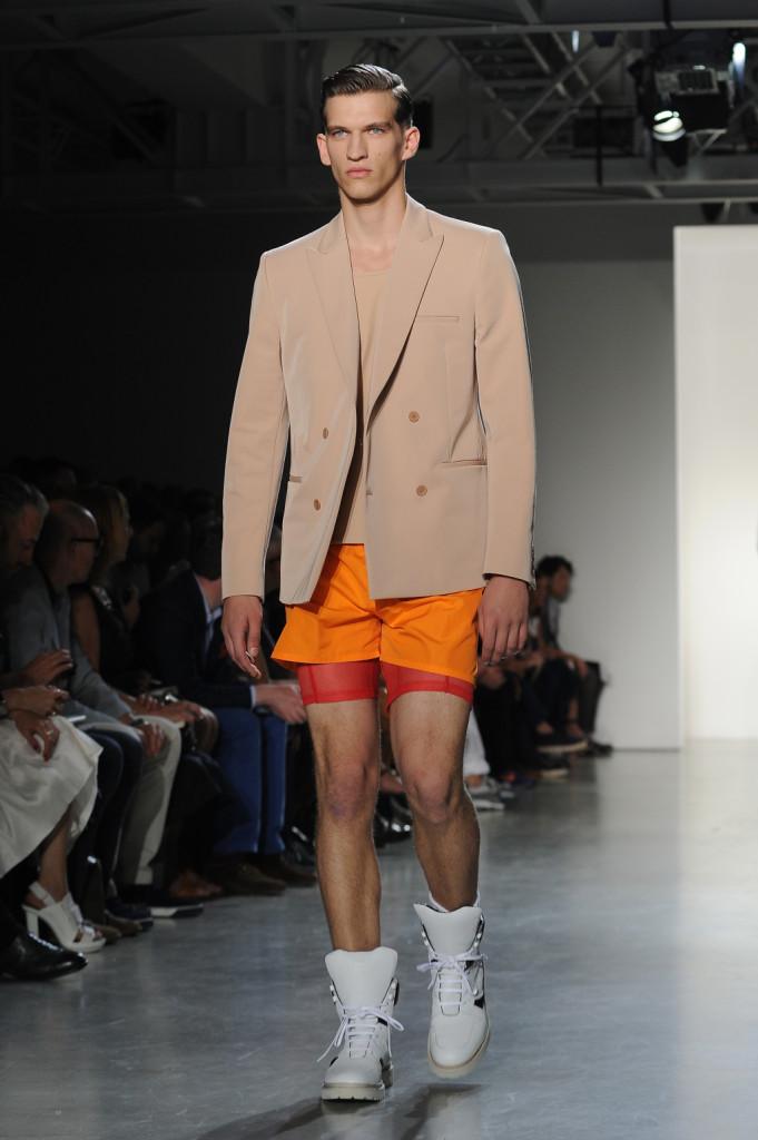 A tutto shorts: se la t-shirt e la giacca si tingono di nude look, per la parte inferiore l'uomo Calvin Klein preferisce shorts colorati e stivali a contrasto