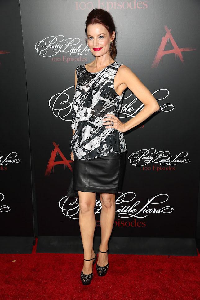 Laura Leighton indossa una gonna in pelle sopra al ginocchio con blusa abbinata