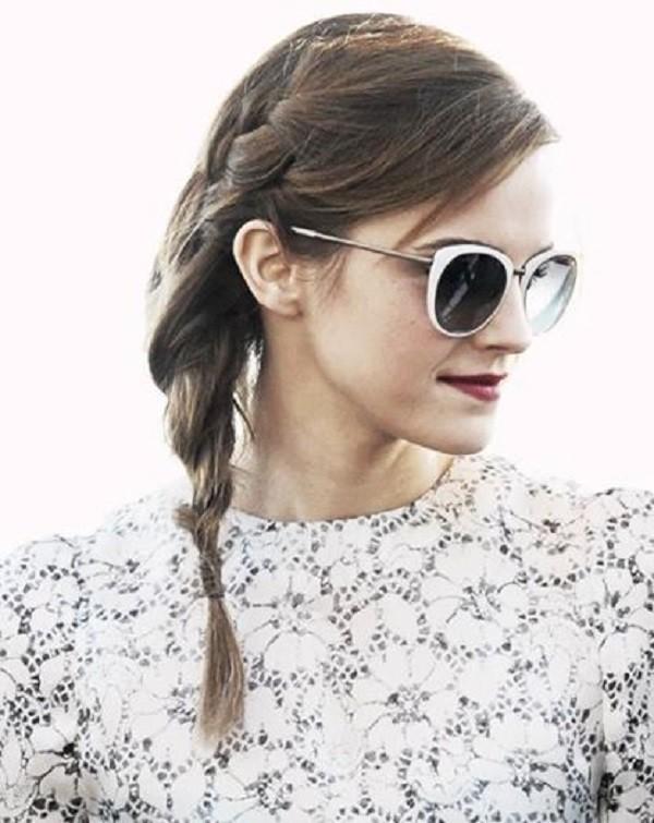 Emma Watson con capelli raccolti in una treccia.