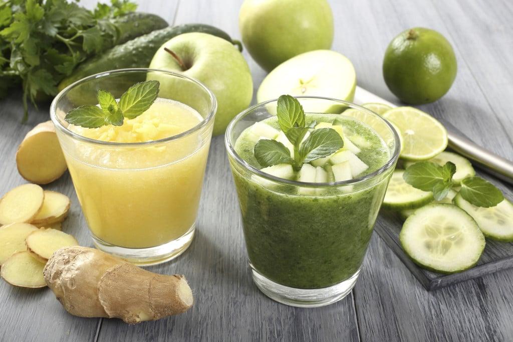 due frullati biologici alla frutta preparati con mela e cetriolo il primo e con limone e zenzero il secondo