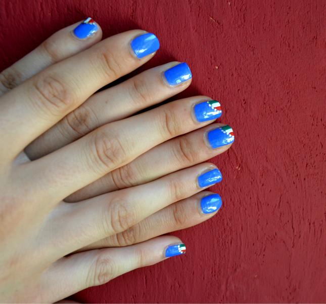 Una panoramica dall'alto della nail art terminata : le unghie decorate poggiano su uno sfondo rosso
