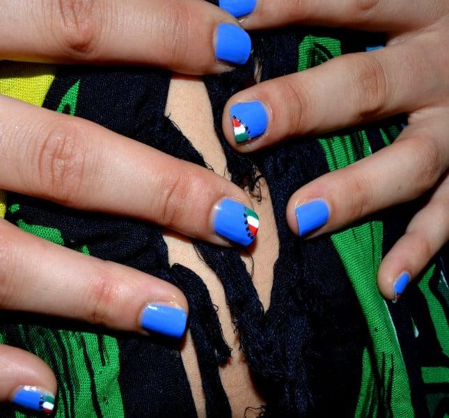 Risultato finale della nail art: le unghie decorate poggiano su un pareo