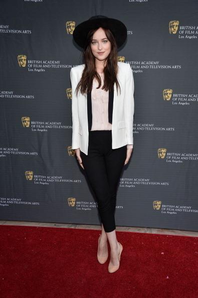 Dakota Johnson indossa un completo bianco e nero con ampio cappello