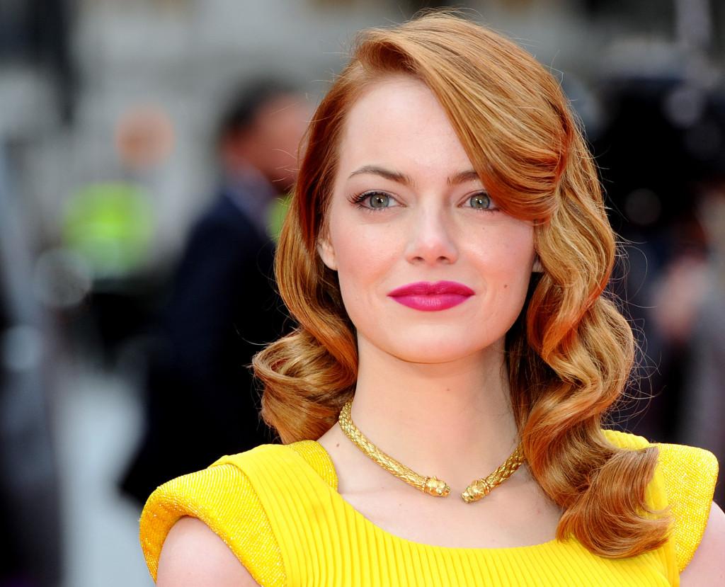 Emma Stone porta la frangia laterale in armonia con i capelli lunghi e ondulati che le incorniciano il viso