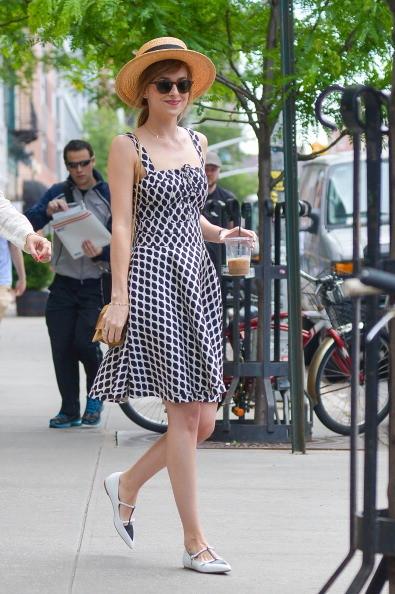 Dakota Johnson indossa un vestito a fantasia con cappello di paglia