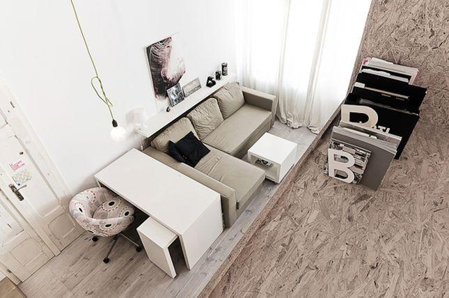 Un angolo studio in soggiorno con scrivania vicino al divano secondo lo studio di architettura polacco 3XA
