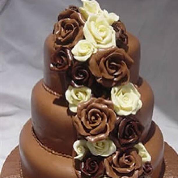 Torta nuziale al cioccolato con decori floreali.