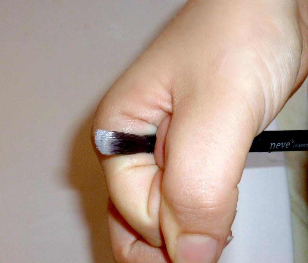 Stringendo il pennello fra il pollice e l'indice, creare una pressione per rimuovere l'eccesso di acqua