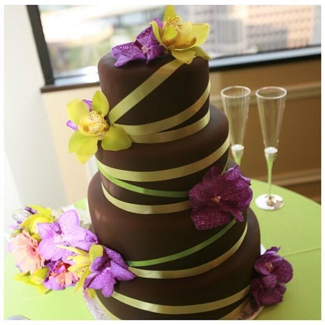 Torta nuziale al cioccolato con decori floreali colorati gialli e viola, per un matrimonio primaverile