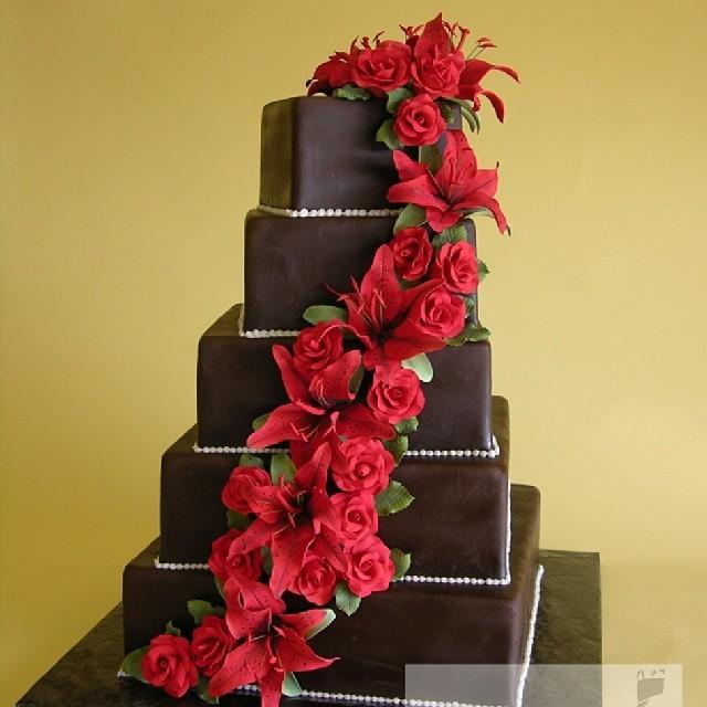 Torta nuziale al cioccolato con decori floreali fatti di rose rosse