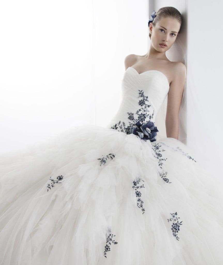 Nel modello Jolies di Nicole Spose una pioggia di fiori blu impreziosisce una nuvola di tulle bianco