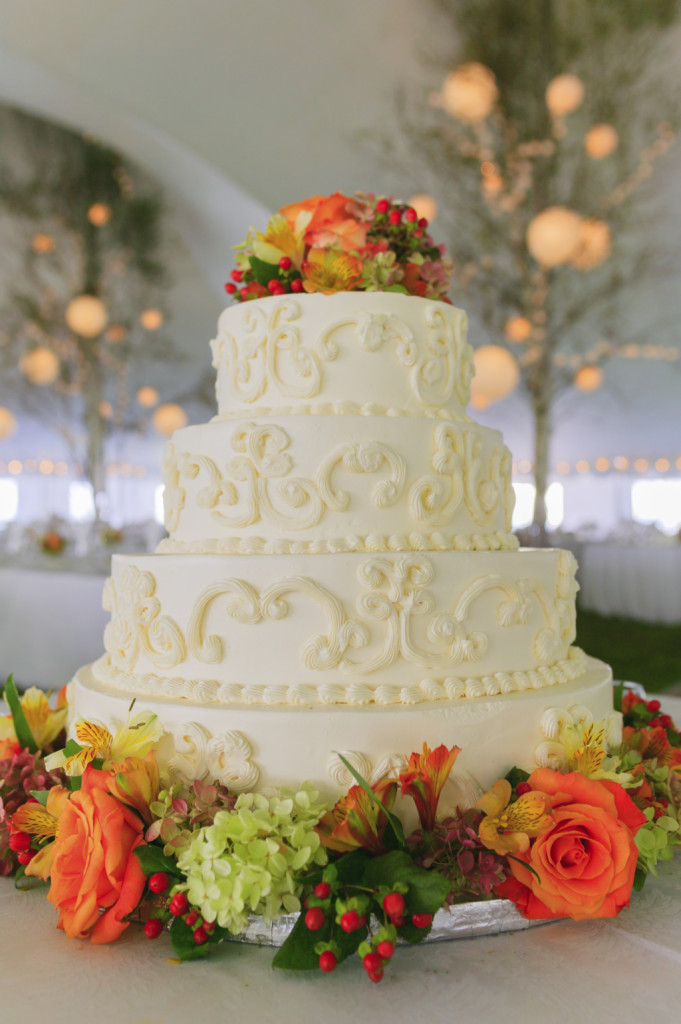torta bianca a quattro piani con rose gialle e arancio, ripiena con cioccolato fondente