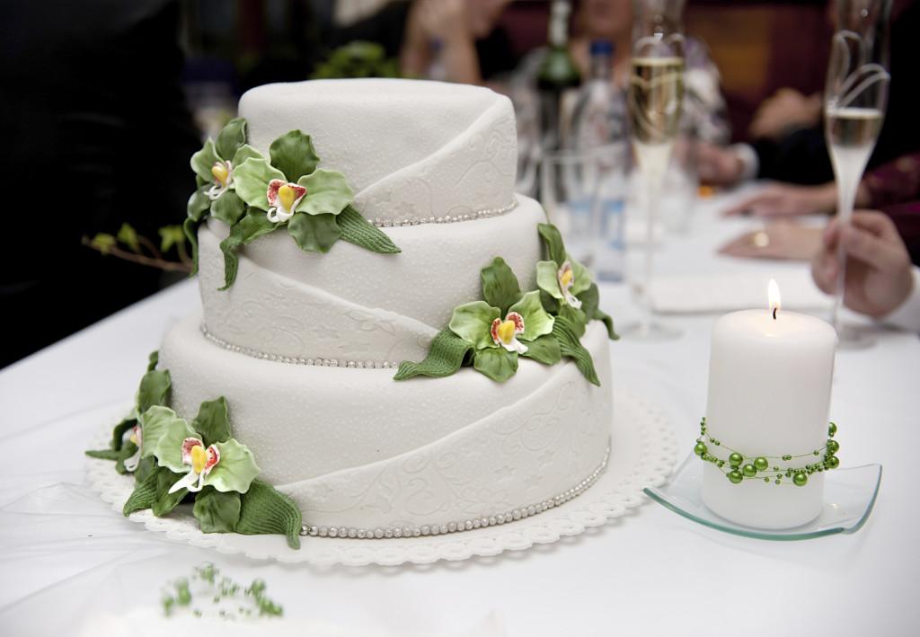 una torta bianca a tre piani con stupende orchidee ed una classica farcitura in panna e crema