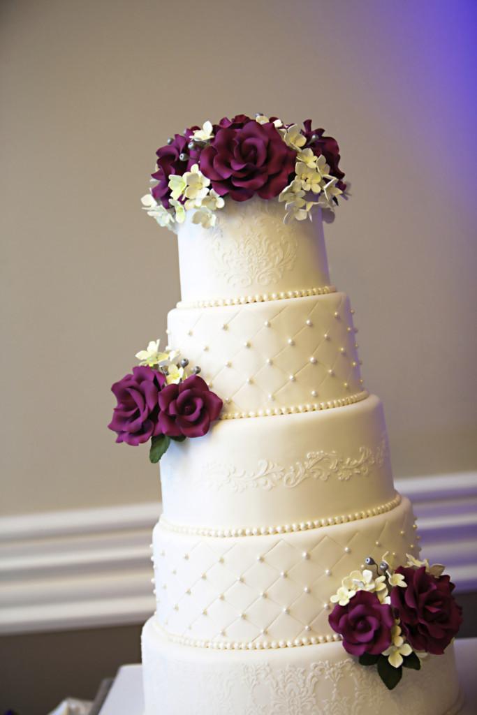 una spettacolare torta nuziale a quattro piani con rose indaco e fiorellini bianchi farcita con crema e more