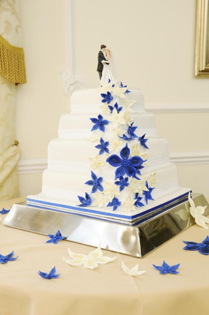 una torta bianca e blu molto spettacolare con inserti blu in pasta di zucchero e crema allo zabaione