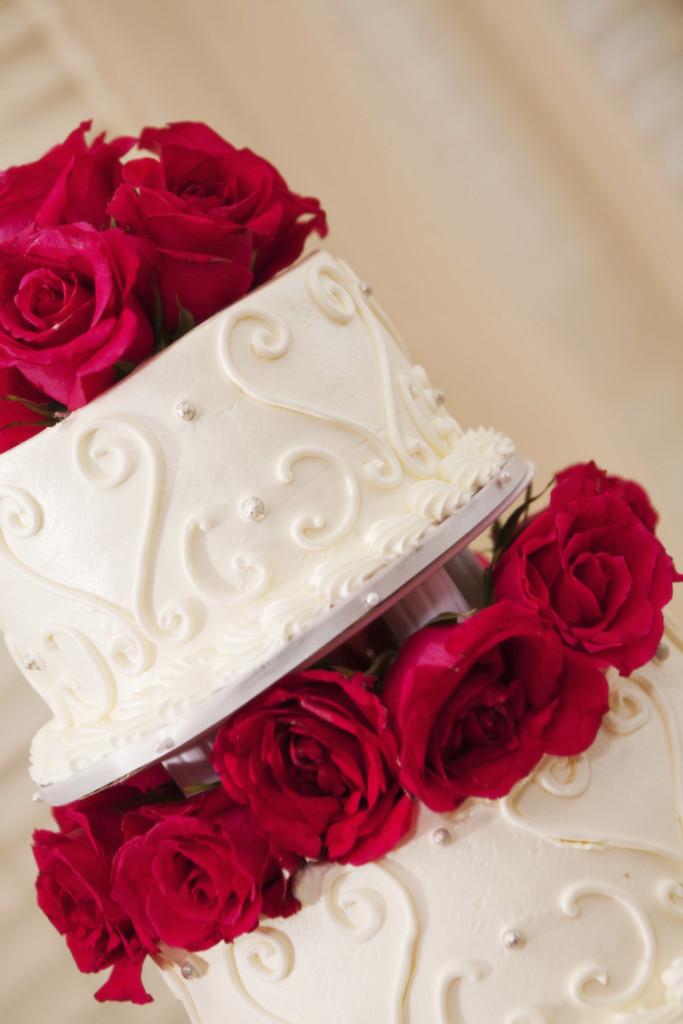 una torta bianca monumentale a tre piani con splendide rose rosse e fucsia, ripiena con panna e fragole