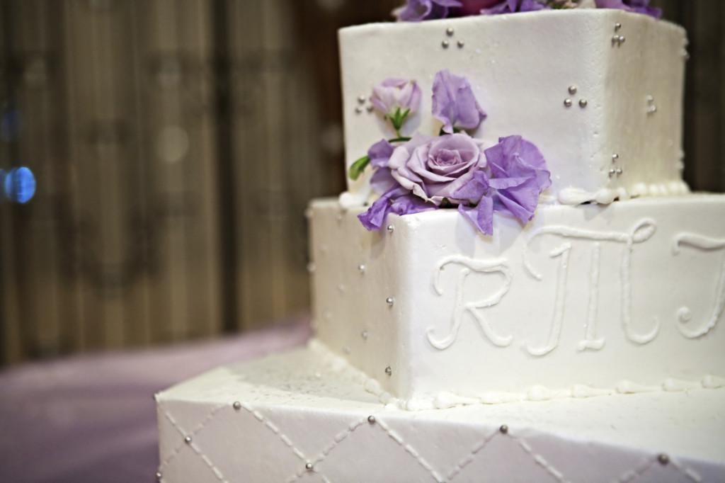 torta bianca e indaco riccamente decorata con rose di un indaco chiaro