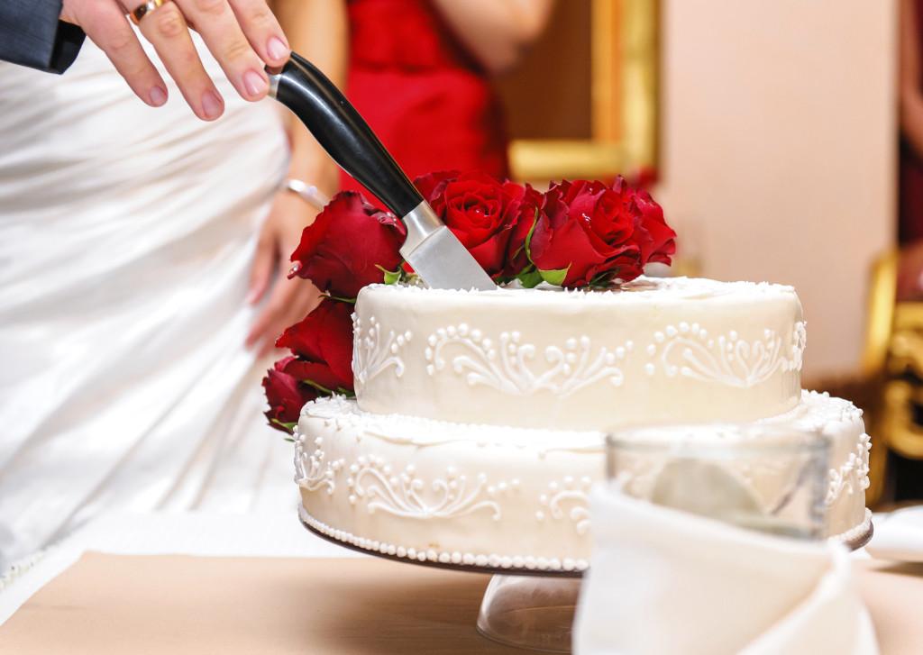 una torta bianca semplice a soli due piani con rose rosse fresche ripiena con crema e fragoline di bosco