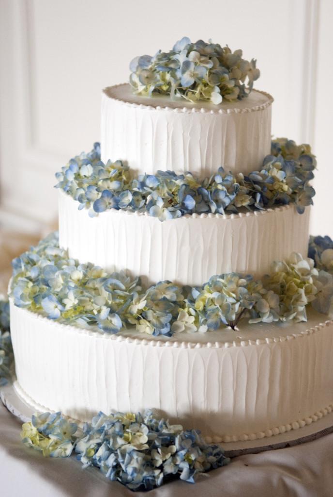 torta bianca a tre strati con base tonda e fiori azzurri, ripiena con crema chantilly