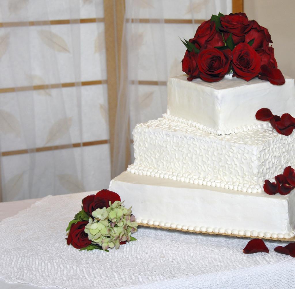 una classica torta bianca a tre piani con base quadrata arricchita da rose rosse fresche