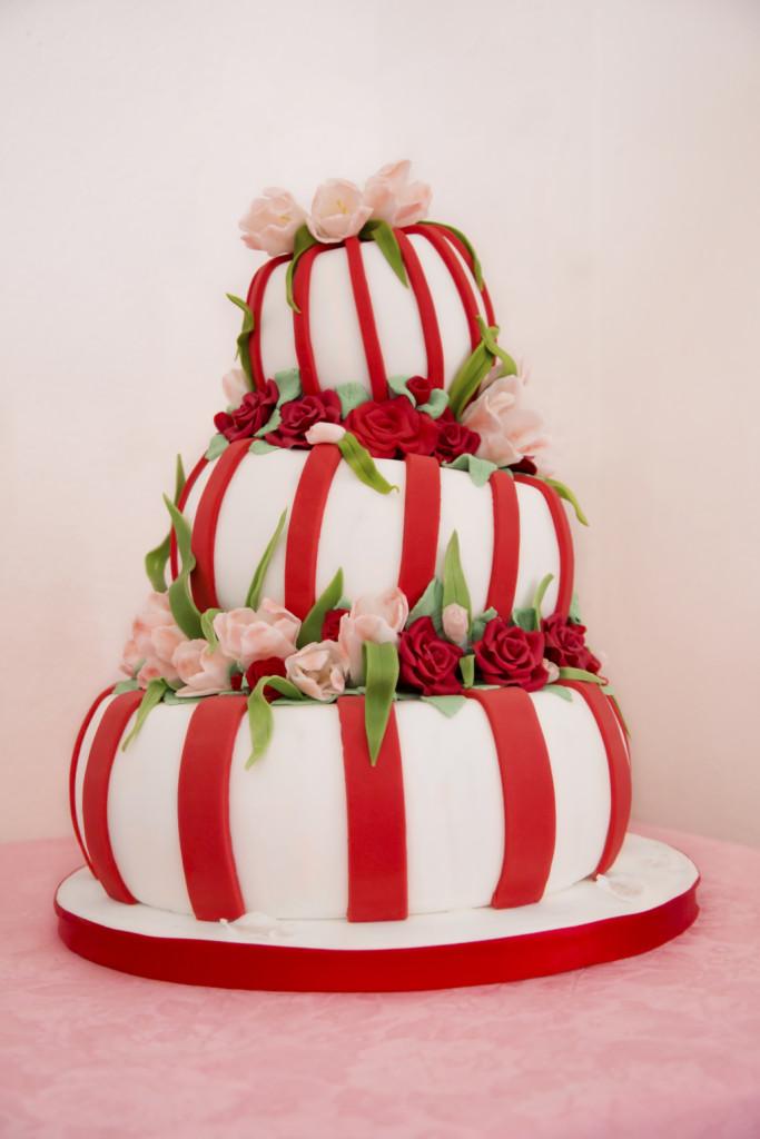 una torta rossa e bianca fuori dal comune con tre piani e roselline rosse e rosa
