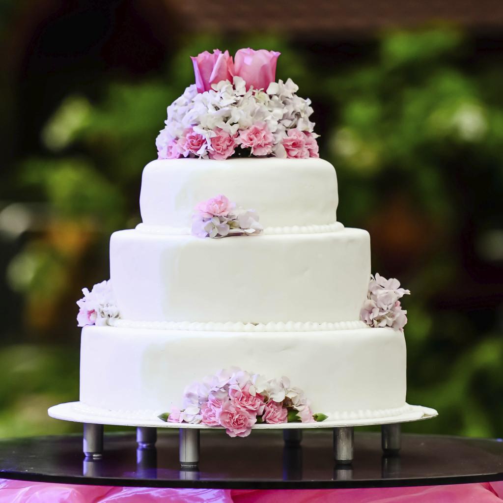 raffinata la torta bianca con roselline indaco e rosa, per donne romantiche