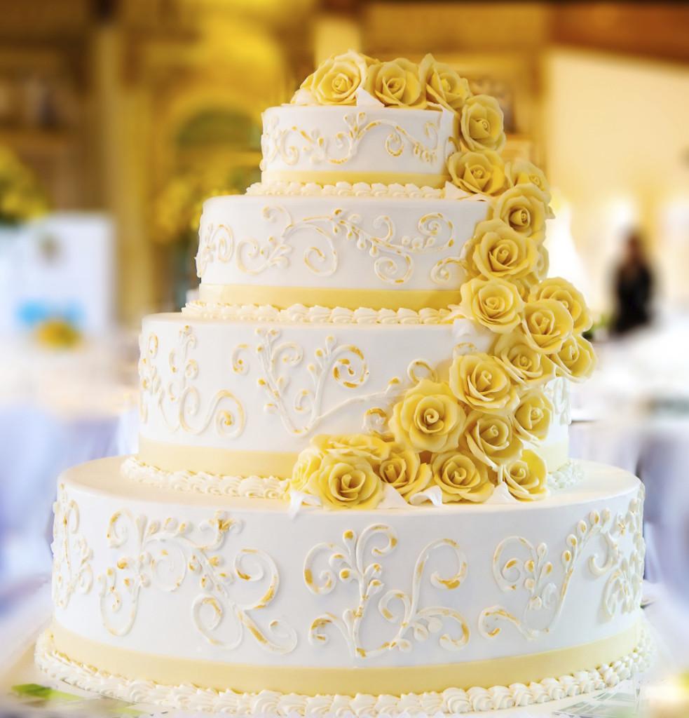 la torta bianca e gialla è riccamente decorata, con inserti in pasta di zucchero e rose gialle commestibili. Provala ripiena con crema al limone oppure lime e cocco